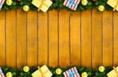 La fila paralela adorna la bola de oro y la caja de la rama spruce con los regalos en la base de madera, marco del diseño de la N Imágenes de archivo libres de regalías