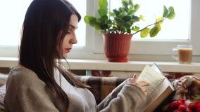 La fille à la fenêtre lisant un livre banque de vidéos