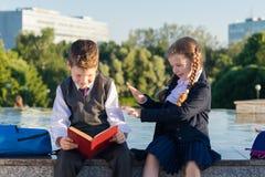 La fille à l'école vêtx distraire un étudiant de lire un livre Photos libres de droits