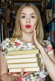 La fille à la bibliothèque avec des livres exprimant la surprise s d'émotion photographie stock