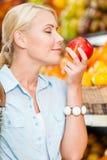 La fille à la boutique choisissant des fruits sent la pomme Photographie stock