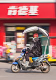 La fille à la mode sur un e-vélo passe le débouché de KFC, Hengdian, Chine Photographie stock libre de droits