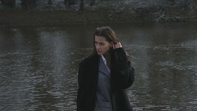 La fille à la rivière le soir dans la lumière foncée banque de vidéos
