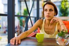 La fille à la table dans le café Photos libres de droits