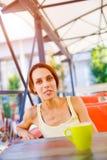 La fille à la table dans le café Images stock