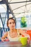 La fille à la table dans le café Photographie stock