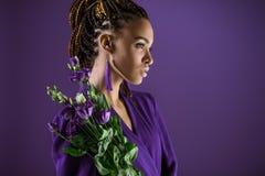 La fille à la mode d'afro-américain posant avec l'eustoma pourpre fleurit, image libre de droits