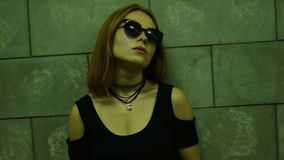 La fille à la mode en verres se tient le soir sur la rue près d'un mur banque de vidéos