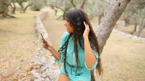 La fille écoutant la musique et chantent émotif et la commande sur le smartpho banque de vidéos