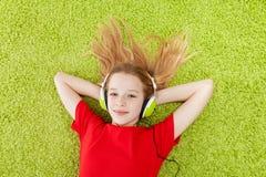 La fille écoute la musique avec des écouteurs en fonction Images stock