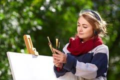 La fille écoute la musique et sélectionne une brosse pour le dessin photographie stock