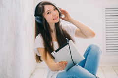 La fille écoute musique se reposant sur le plancher dans le studio Tandis qu'hôte Photo libre de droits