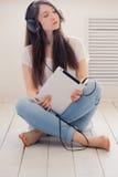 La fille écoute musique se reposant sur le plancher dans le studio Tandis qu'hôte Photo stock
