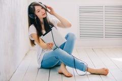 La fille écoute musique se reposant sur le plancher dans le studio Tandis qu'hôte Photos stock
