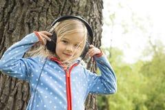 La fille écoutent la musique sur des écouteurs Images libres de droits