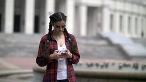 La fille écrit quelque chose au téléphone, causerie sur l'Internet, correspondance photos stock