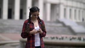La fille écrit quelque chose au téléphone, causerie sur l'Internet, correspondance images stock