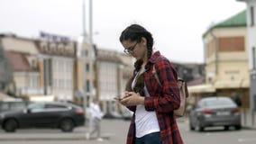 La fille écrit quelque chose au téléphone, causerie sur l'Internet, correspondance photographie stock libre de droits