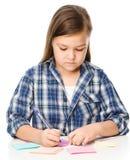 La fille écrit sur des autocollants de couleur utilisant le stylo Images stock