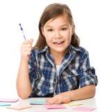 La fille écrit sur des autocollants de couleur utilisant le stylo Photographie stock