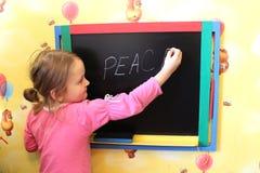 La fille écrit sur le mot de tableau noir la paix Images stock