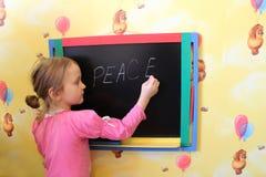 La fille écrit sur un tableau noir un mot la paix Images stock