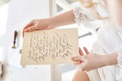 La fille écrit une lettre à son homme aimé, s'asseyant à la maison à la table dans une robe, une pureté et une innocence de lumiè Photos stock