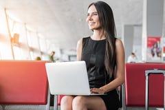 La fille élégante agréable s'assied sur le banc rouge avec l'ordinateur Photo stock