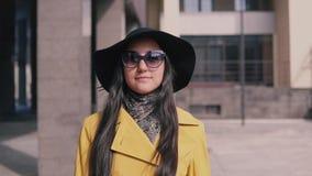 La fille élégante avec une bonne humeur en chapeau jaune et verres d'imperméable vient avec le bagage banque de vidéos