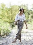 La fille élégante d'adolescent dans le pantalon léger roulé marche nu-pieds sur le sable Images stock