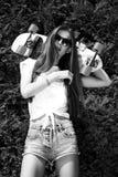 La fille élégante dans des lunettes de soleil pose avec le longboard de images libres de droits
