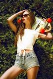 La fille élégante dans des lunettes de soleil pose avec le longboard de Image libre de droits