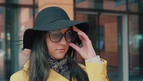 La fille élégante dans un chapeau enlève des verres et des regards dans la distance banque de vidéos