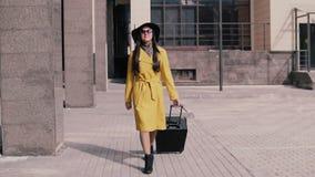 La fille élégante en chapeau jaune et verres d'imperméable va de pair avec le bagage et le sourire banque de vidéos