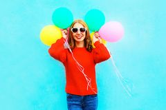 La fille élégante fraîche tient les ballons à air colorés sur le bleu Image libre de droits