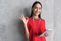 La fille élégante joyeuse utilise le dispositif moderne photos libres de droits