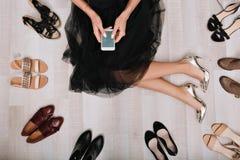 La fille élégante s'asseyant sur le plancher dans un vestiaire avec le smartphone dans des mains, écrit le message, entouré par a images libres de droits