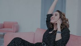 La fille ?motive et avec du charme s'assied sur le sofa et parler de bonnes nouvelles ? son t?l?phone portable Elle est heureuse  banque de vidéos