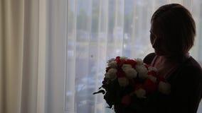La fille a été donnée un grand bouquet des roses, silhouette, cadeau banque de vidéos