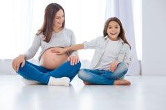 La fille étonnée adorable sent des mouvements de bébé dans le ventre de mamans Photographie stock libre de droits