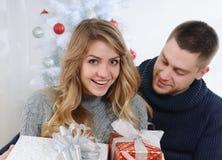 La fille étonnée par son ami avec des cadeaux s'approchent de l'arbre de Noël Photos stock