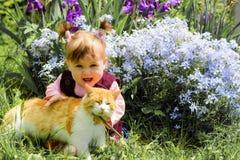 La fille étonnante joue avec un chat de minerai en fleurs Images stock