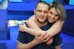 La fille étreint l'homme et sourit dans le bowling du club Photographie stock libre de droits