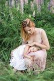 La fille étreint la mère, photosession de famille en fleurs Photographie stock libre de droits