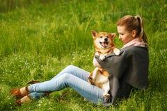 La fille étreint le chien Shiba Inu Images stock