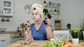 La fille étroite avec le masque sur le visage s'assied au miroir mange de la nourriture malsaine de concept de chocolat banque de vidéos