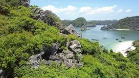 La fille étroite de vue monte vers le bas les roches dangereuses contre la baie d'océan banque de vidéos