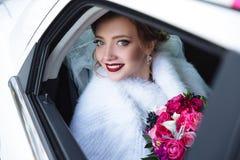 La fille a abaissé la fenêtre dans la voiture et a souri Le portrait en gros plan d'un modèle dans un manteau de fourrure blanc s photos libres de droits
