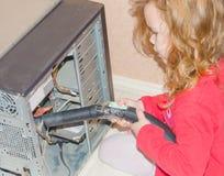 La fille absorbe l'aspirateur d'ordinateur personnel photographie stock