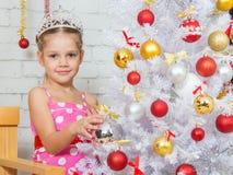 La fille accroche des boules sur un arbre de Noël neigeux de nouvelles années Photographie stock